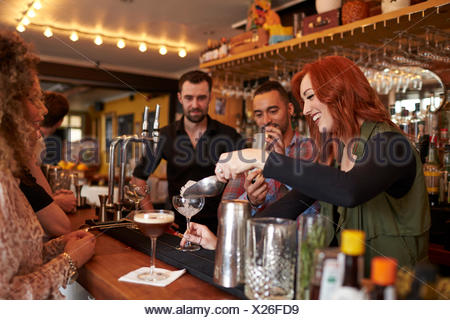 Woman Learning How To Mix Cocktail At Lesson In Bar - Stock Photo