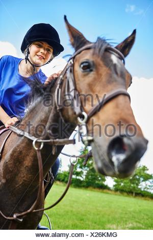 Low angle view of girl on horseback wearing riding hat smiling - Stock Photo