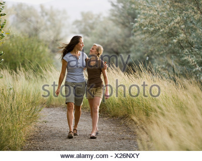 woman and young woman walking with arm around each other. - Stock Photo