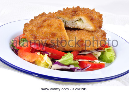 garlic chicken kiev with mixed leaf salad ready to eat - Stock Photo