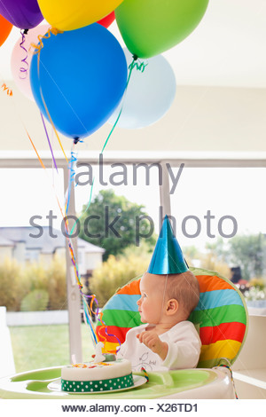 Baby in high chair with birthday cake and balloons - Stock Photo