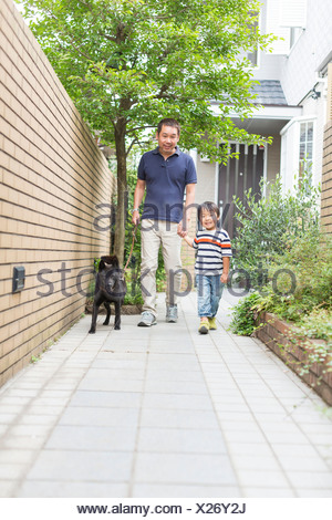 Father and son walking dog on path - Stock Photo