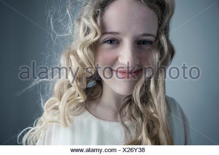 Close up portrait smiling Caucasian young woman with messy curly blonde hair - Stock Photo