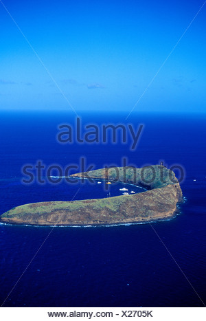 Aerial view of Molokini with boats moored off this partially exposed crater. Molokini has fantastic snorkeling and is a popular - Stock Photo