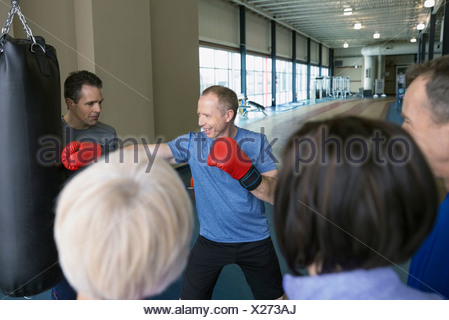 Man learning to box at gym - Stock Photo