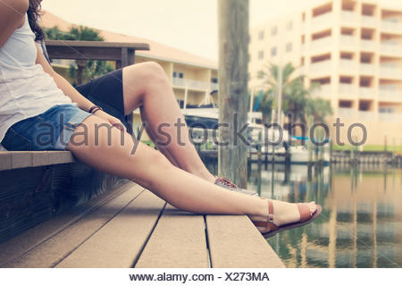 Young woman and young man sitting on jetty - Stock Photo