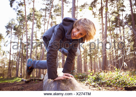 Boy jumping over a tree trunk in forest - Stock Photo