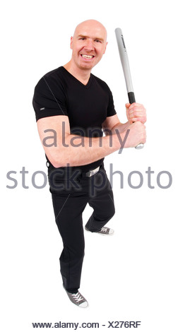 bald headed man holding a baseball bat in his hands, laughing into the camera - Stock Photo