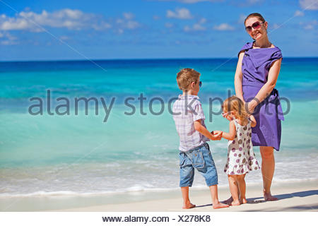 a young mother standing with her little children on tropical beach - Stock Photo