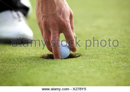 Person holding golf ball, close-up - Stock Photo