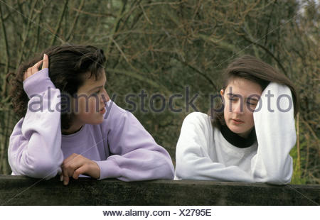 two teenage girls leaning over gate having conversation - Stock Photo
