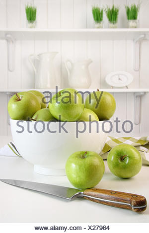Green apples in bowl on table in kitchen - Stock Photo