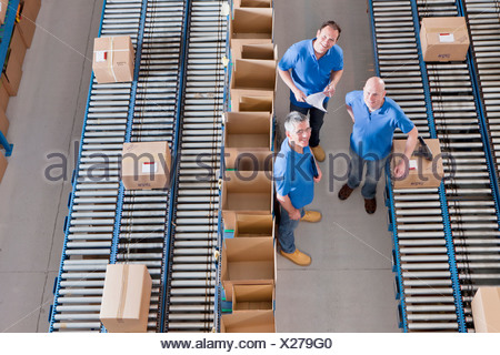 Portrait of smiling workers among boxes on conveyor belts in distribution warehouse - Stock Photo