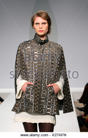 Allegra Hicks London Ready to Wear Autumn Winter Model blonde hair wearing light brown cape funnel neck and silver geometric - Stock Photo