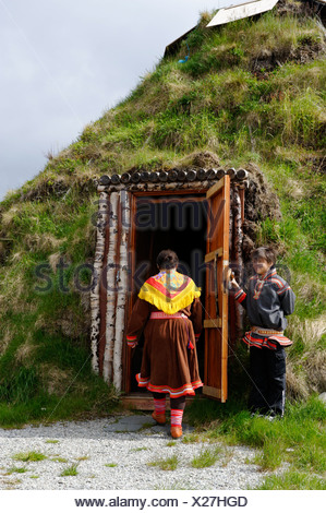 Woman wearing the traditional costume of the Sami People in front of her earth covered lodge, Hammerfest, Norway, Scandinavia,  - Stock Photo