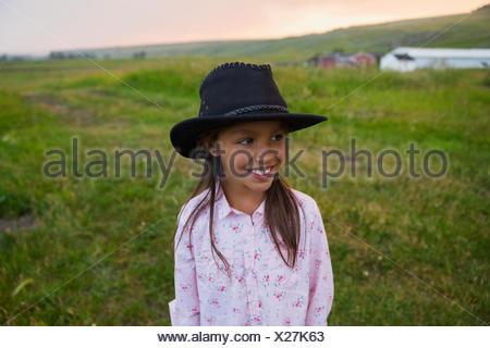 Smiling girl in black cowboy hat - Stock Photo