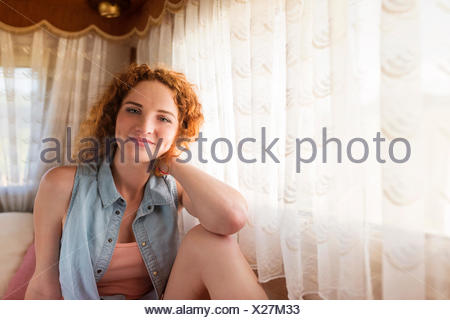 Portrait of smiling young woman sitting in a caravan - Stock Photo