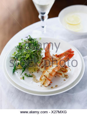 Plate of prawn salad with potatoes and micro herbs - Stock Photo