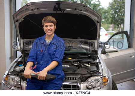 Female mechanic with diagnostic computer by open bonnet of car, smiling, portrait - Stock Photo