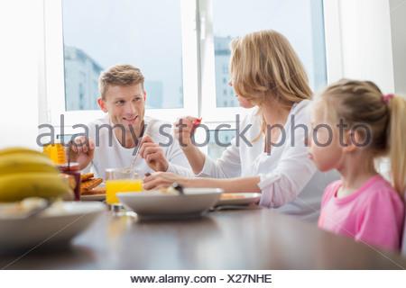 Happy family of three having breakfast at table - Stock Photo