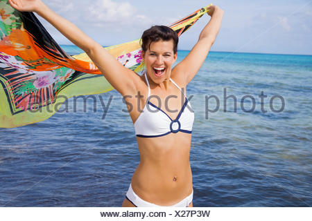 lachende glückliche junge frau mit buntem tuch am meer strand im sommer urlaub freiheit lebensstil gesundheit glück - Stock Photo