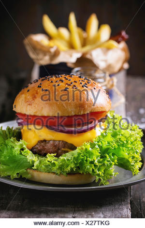 Fresh homemade burger with black sesame seeds on wooden cutting board with French fries, served with ketchup sauce in glass jar - Stock Photo