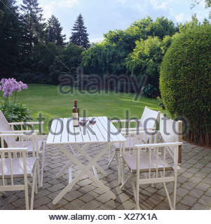 White garden furniture on paved patio overlooking lawn in large country garden - Stock Photo
