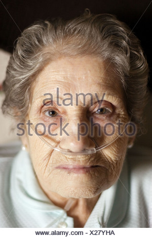Elderly woman using a nasal oxygen cannula - Stock Photo