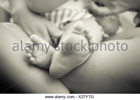 Baby and parent, close-up of baby's feet - Stock Photo