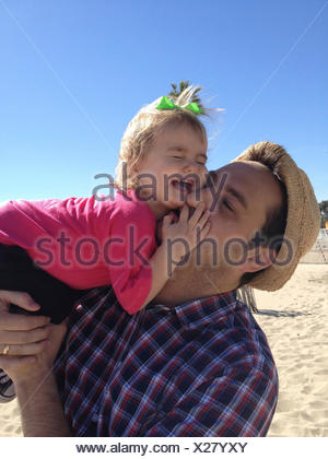 Father and daughter (18-23 months) having fun on beach - Stock Photo
