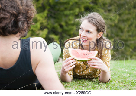 Mid adult couple eating watermelon in filed - Stock Photo