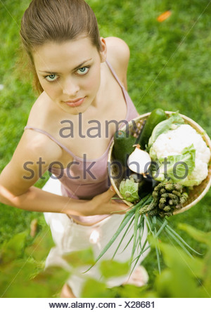 Woman holding basket of fresh vegetables, high angle view - Stock Photo