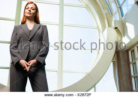 Confident businesswoman with ginger hair wearing grey suit standing beside window portrait low angle view - Stock Photo