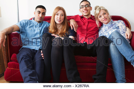 Four young adults sitting on sofa - Stock Photo