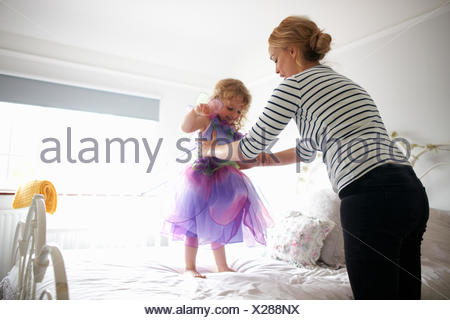 Young girl dressed in fairy costume, standing on bed, mother lifting her - Stock Photo