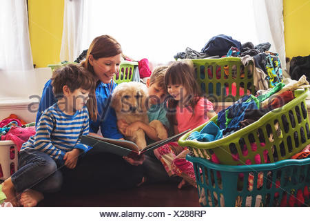 Smiling mother reading to three children and golden retriever puppy dog surrounded by laundry baskets - Stock Photo