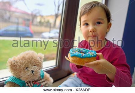 little girl eating donuts with her toy friend. - Stock Photo