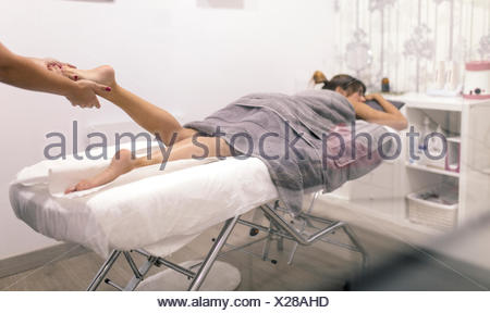 Young woman receiving a foot massage - Stock Photo