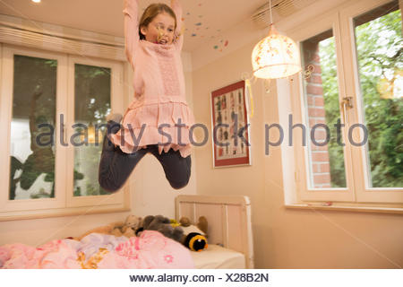 Girl having fun jumping mid air from bed in bedroom - Stock Photo