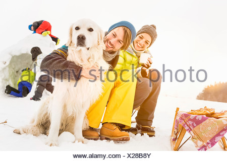 Parents with dog and children playing in background - Stock Photo