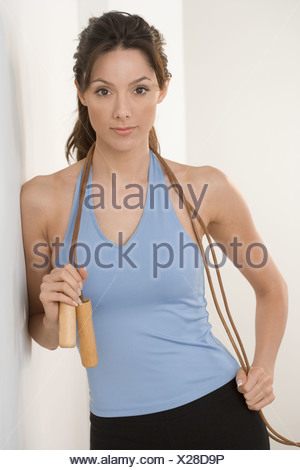 Woman with jump rope leaning on wall - Stock Photo