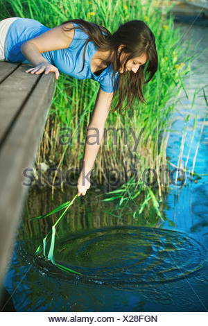 Girl playing with reed in the water - Stock Photo