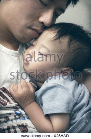 Boy sleeping in father's lap - Stock Photo