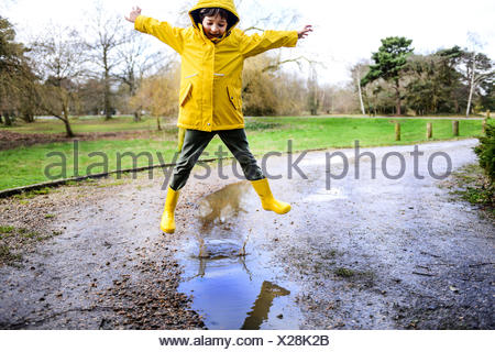Boy in yellow anorak jumping above puddle in park - Stock Photo