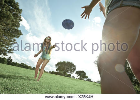 Two women playing game of Frisbee in park - Stock Photo