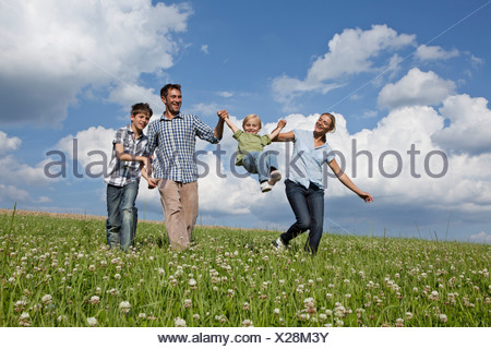 Germany, Bavaria, Altenthann, Family playing together in meadow - Stock Photo