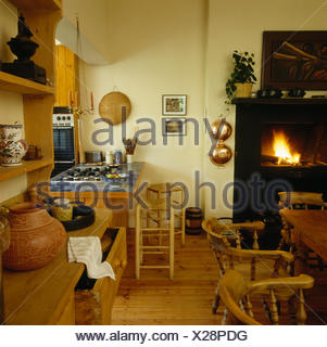 Rush seated wooden stools at tiled breakfast bar in a seventies kitchen with a lighted fire in the fireplace - Stock Photo