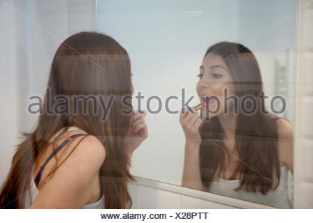 Young adult woman applying make up in mirror - Stock Photo