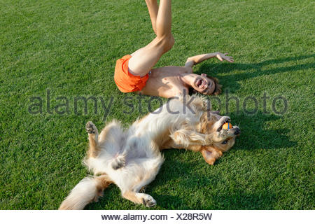 Teenage boy playing with Golden Retriever on lawn - Stock Photo