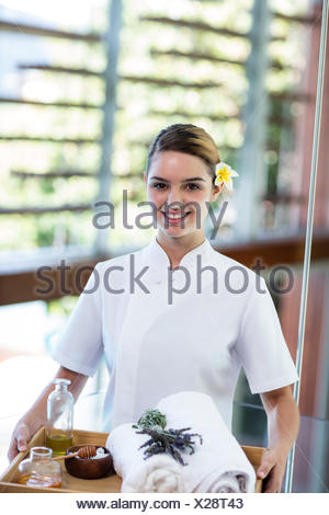 Smiling masseuse holding a tray - Stock Photo
